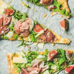 Pieces of fig, prosciutto, arugula and sage flatbread pizza
